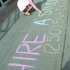 Katie Fabris, Youth Service Officer with Service Canada  uses sidewalk chalk to promote the hire a student number on the sidewalk infront of Service Canada offices on 4th Avenue. Citizen photo by Brent Braaten        Aug 4 2011